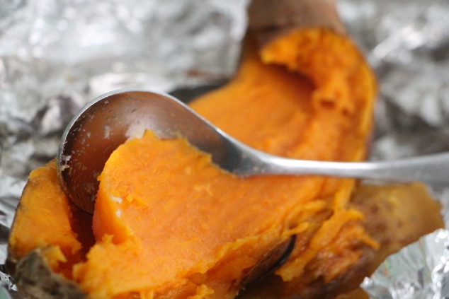 scooping sweet potato flesh