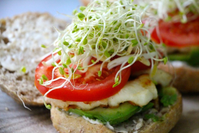 adding sprouts onto sandwich