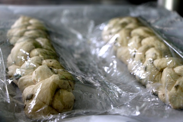 braided challah covered with plastic wrap