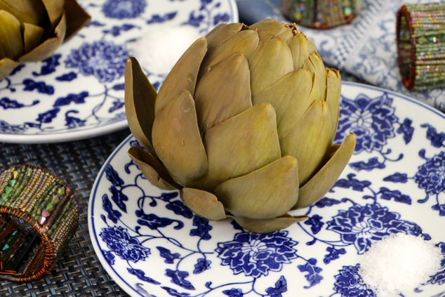 boiled artichokes served on plates with side of salt