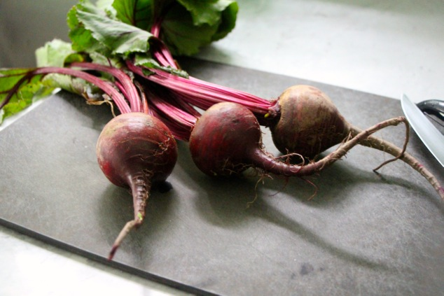 three fresh beets on a cutting board