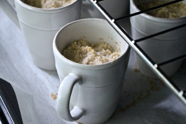 individual crumbles in mugs baking in the oven