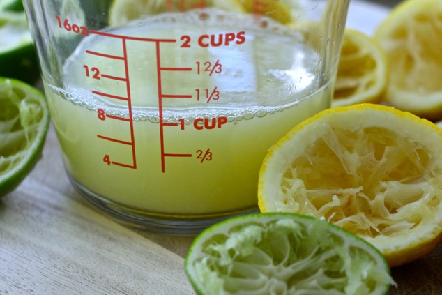 lemon and lime juice in measuring cup up close