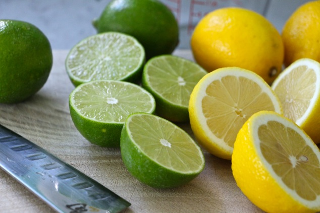 lemons and limes halved on a cutting board
