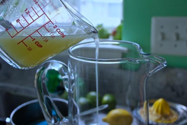 pouring lemon juice into a pitcher