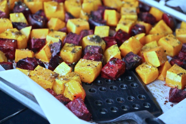 roasting beets and butternut squash on tray with slotted turner