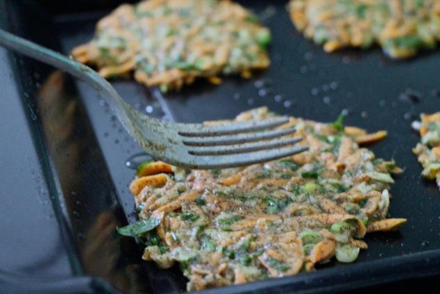 flattening sweet potato kohlrabi latkes onto griddle