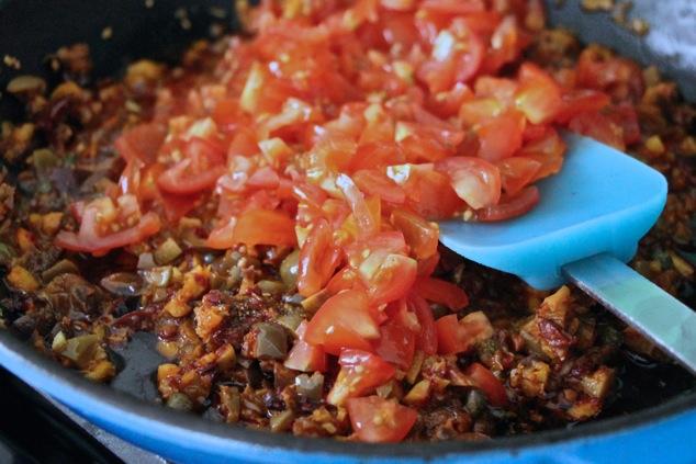 adding chopped cherry tomatoes