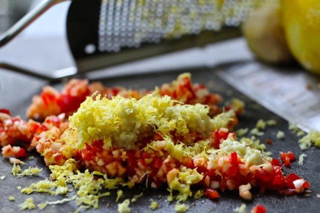 adding lemon zest to chopped garlic and hot pepper
